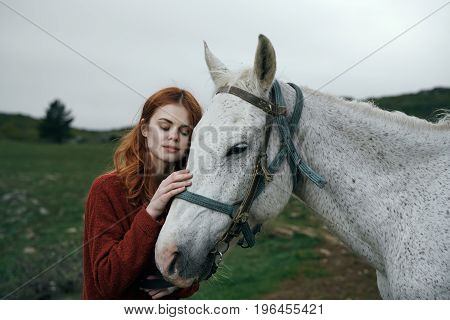 Young beautiful woman walking in the mountains with a horse.