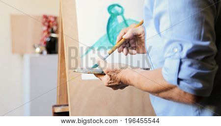 Elderly woman painting for hobby. Active senior person at art school. Closeup of old female hand with brush and palette mixing color paints