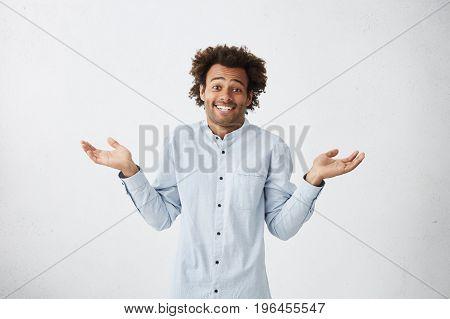 Portrait Of Uncertain Careless Young African-american Employee Wearing Long Shirt Shrugging Shoulder