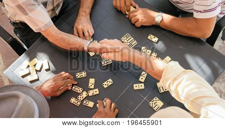 Senior Friends Shaking Hands Winning Game Of Domino