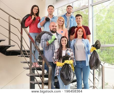 Young volunteers with garbage bags on staircase