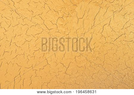 Gold texture with crackling effect. Decorative plaster. Interior wall decoration. Top view.