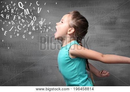 Little girl and letters on grunge background. Speech therapy concept