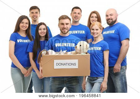 Young volunteers with box of donations on white background