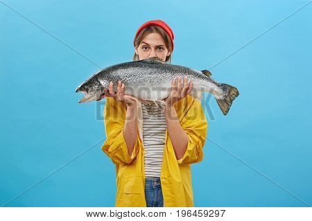 Pretty Housewife Holding Huge Fish Caught By Her Husband. Beautiful Woman Dressed In Yellow Raincoat