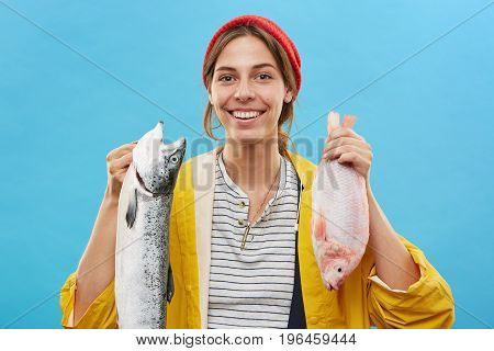 Successful Female Angler Holding Two Big Fish In Hands, Smiling At Camera While Having Good Mood Aft