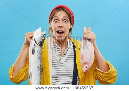 Surprised Female Angler Holding Fish Looking With Wide Opened Eyes And Mouth Isolated Over Blue Back