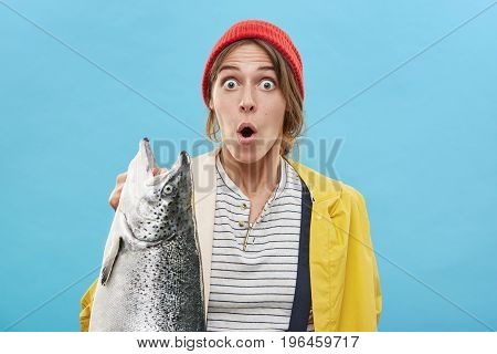 Attractive Amazed Female Wearing Red Hat And Yellow Anorak Holding Huge Fish In Hand Having Shock To