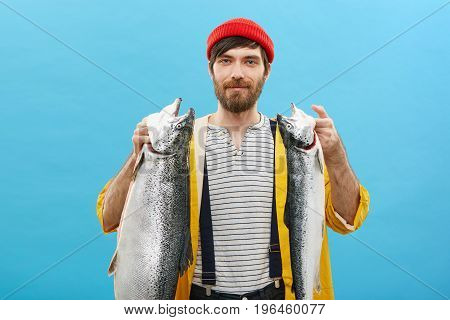 Satisfied Caucasian Man With Thick Beard Having Happy Expression While Holding Two Huge Fish Having