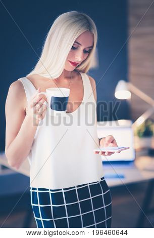 Young businesswoman sitting on the desk with with cup.