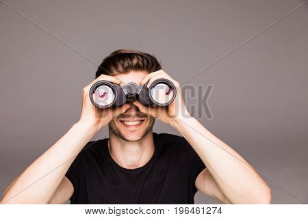 Young Handsome Man Searching With Binoculars Near Laptop At Office Work Place . Work Concept
