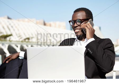 Elegant Financier In Trendy Eyewear Wearing Formal Black Suit Having Conversation Over Smart Phone R