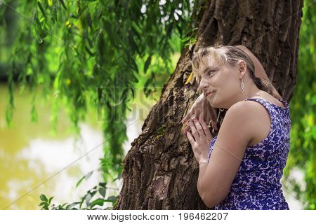 Young beautiful woman in a picturesque place, thoughtful leaning on a tree