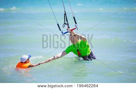 Male kite surfer helping young boy to come closer in water. Teaching how to ride kite. Active family vacations concept.