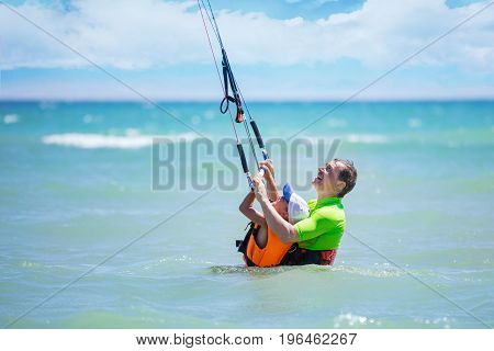 Male kite surfer teaching young boy how to ride kite. Active family vacations concept.