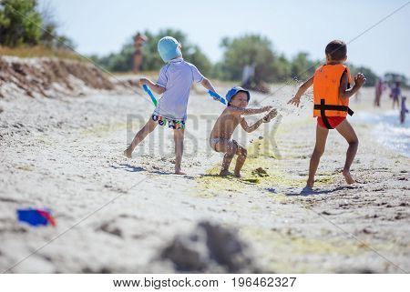 Two older boys throwing sand at younger one. Children's aggression bullying behavior. Brothers playing on beach. poster