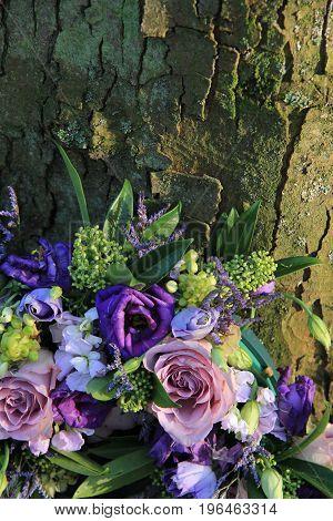 Purple sympathy flowers or funeral flowers near a tree