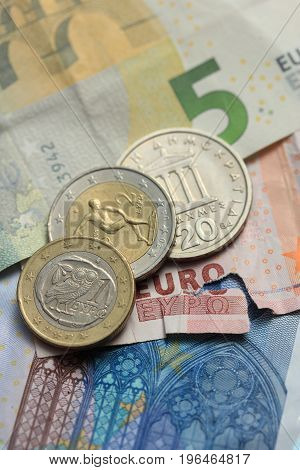 Euro crisis a vintage Greek Drachma coin and a torn euro note