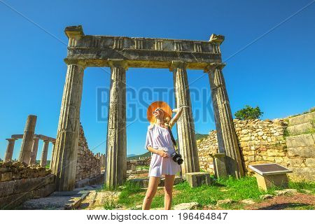 Blonde woman photographer carrying her camera under the columns of Ancient Messene Historical Site in Peloponnese, Greece, Europe. Seductive travel photographer in greek dress and sun hat