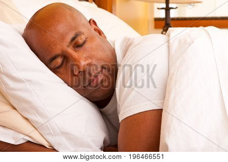 Mature African American man getting a good nights rest.