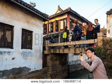 Suzhou, China - Nov 5, 2016: Visitors gather at the stone bridge at the historic Zhouzhuang Water Town. A famous Chinese movie was filmed utilizing this bridge.