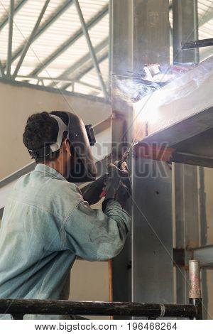 Man Weld A Metal With A Welding Machine.