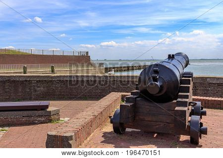 A canon on a defense wall near the sea