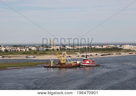 A barge with a crane on it being pushed by a tugboat close to Atlantic City and Brigantine, New Jersey