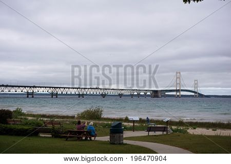 MACKINAW CITY, MICHIGAN / UNITED STATES - JUNE 18, 2017:  Visitors may sit in Alexander Henry Park, and enjoy the view of the Mackinac Bridge, which spans the Straits of Mackinac, to connect Michigan's Lower and Upper Peninsulas.
