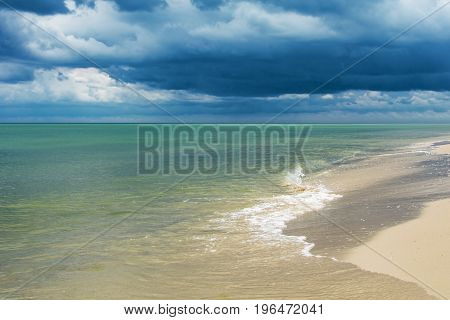 Seaside with small waves and dark clouds over water.
