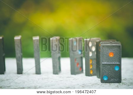 Soft Focus - Domino Effect Concept : Row of black dominoes on concrete floor and green bush with bokeh and sunlight background. (Autumn filter effect)
