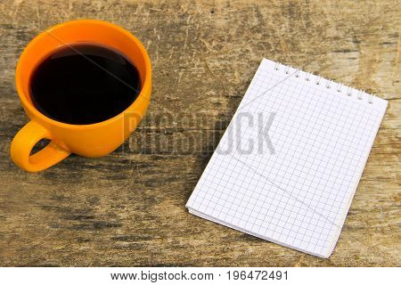 Cup Of Coffee With Blank Notepad On Wooden Table