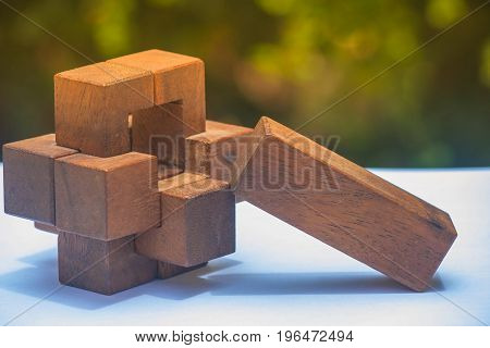 Business Teamwork Concept : Wooden Brain Teaser or Wooden Puzzles on white floor and green bush with sunlight background. (Autumn filter effect)