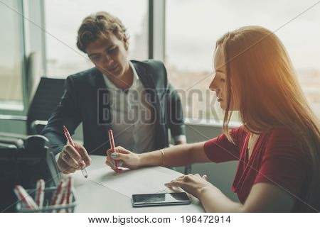 Attractive man entrepreneur having work conversation with his female beautiful co-worker businesswoman explaining her colleague new development strategy using sheet of paper and pen during meeting