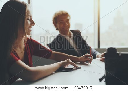 Office work meeting during discussion of something funny: businesswoman in red dress is smiling and her boss in defocused background is laughing while they sitting at the table in room near window