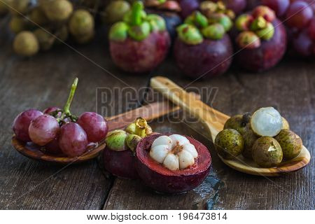 fresh logans mangosteen and grapes on wood floor