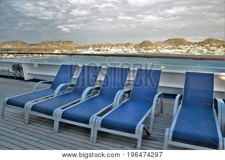 Lounge chairs on a cruise ship deck with mountain and ocean views of the tropical island of St. Kitts