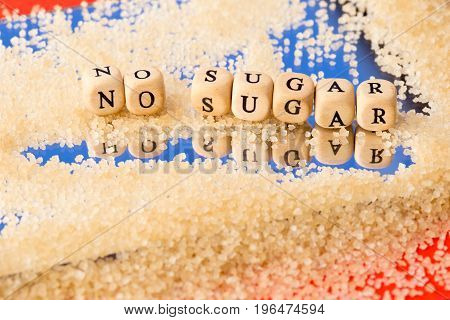 No Sugar - In Wooden Block Letters With Granules Of Sugar On Mirror Background