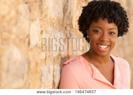 African American woman with curly hair smiling outside.