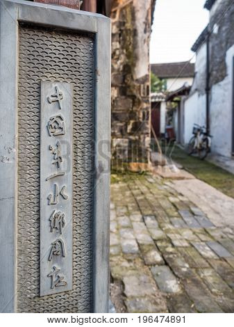 Suzhou, China - Nov 5, 2016: At the ancient Zhouzhuang Water Town, with a history of over 900 years. Plaque beside a path marks this as China's Number One Water Town in Chinese characters.