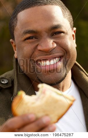 Happy young African American man smiling outside.