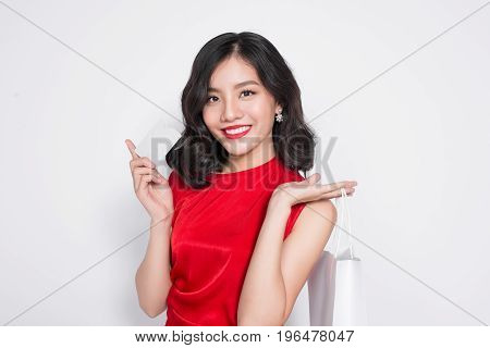 Beautiful Asian Woman Wearing A Red Dress With Shopping Bag Standing Over White.