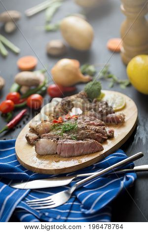 Grilled Red Beef Meat Sliced With Lemon And Carrot On Wooden Plate