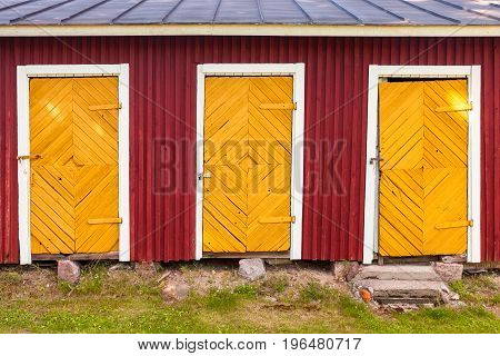 Three Yellow Locked Doors In Red Rural Barn