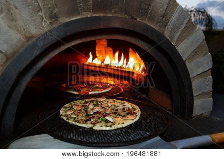 pizza prepares in old stove near fire