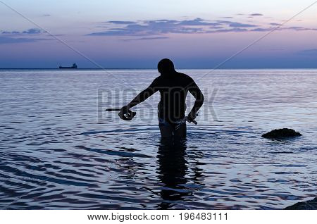 Underwater hunter on the beach preparing to dive . Fishing in the Black sea . Sunset.