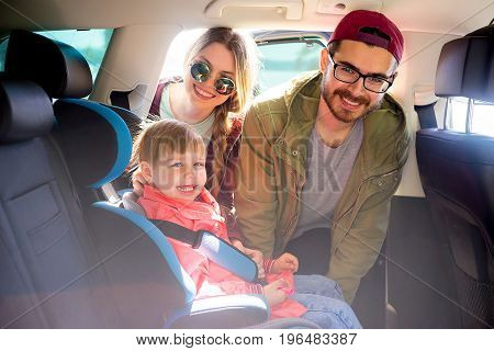 Parents helping their daughter to a baby seat