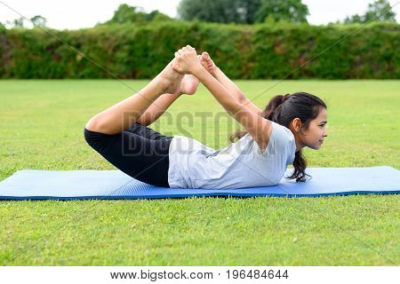 Teenage Girl Practising Yoga Outdoors