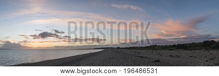 Sunset Panorama Over Shingle Beach With Colorful Vibrant Sky And Clouds