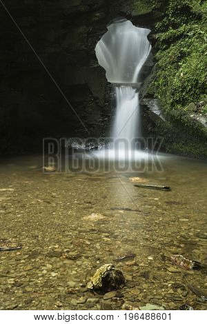 Beautiful Flowing Waterfall With Magical Fairytale Feel In Lush Green Forest Location